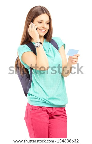 Female student with a school bag talking on a cell phone and holding a credit card isolated on white background - stock photo
