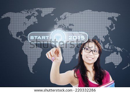 Female student with a start button to start her dream in future 2015 - stock photo