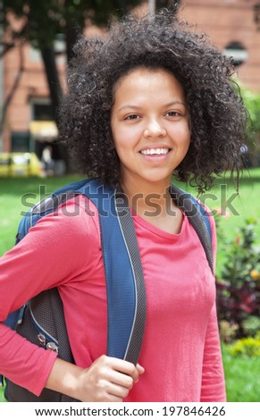 Female student with curly hair looking at camera - stock photo