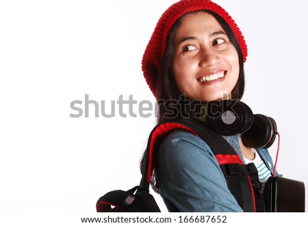 Female student with headphones and holding a laptop - stock photo
