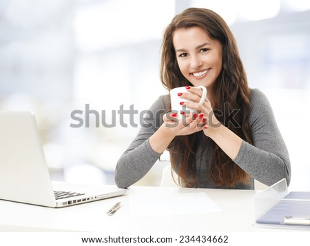 Female student with laptop working on her presentation while drinking tea. - stock photo