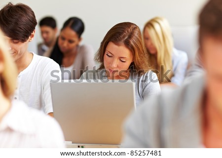 Female student working at laptop in university - stock photo