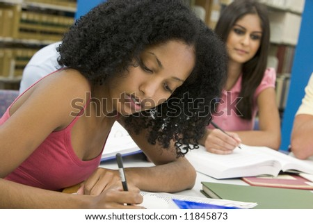 Female student working on essay in library - stock photo