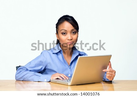 Female student working on her laptop appears bored while looking at the camera. Horizontally framed photograph - stock photo