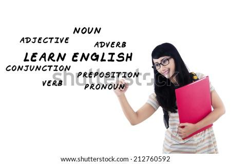 Female student writes english language materials on whiteboard - stock photo