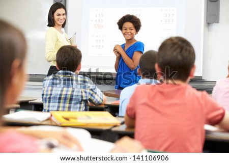 Female Student Writing Answer On Whiteboard - stock photo