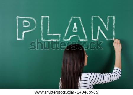 female student writing the word plan on blackboard - stock photo