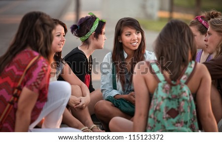 Female students talking outdoors on the sidewalk - stock photo