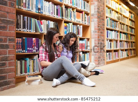 Female students with a book in a library - stock photo