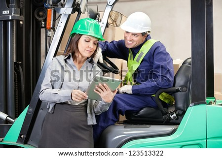Female supervisor and forklift driver using digital tablet at warehouse - stock photo