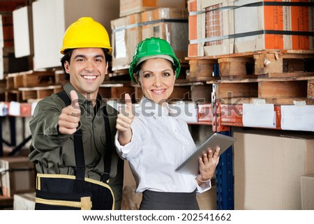 Female supervisor with digital tablet and foreman gesturing thumbs up at warehouse - stock photo