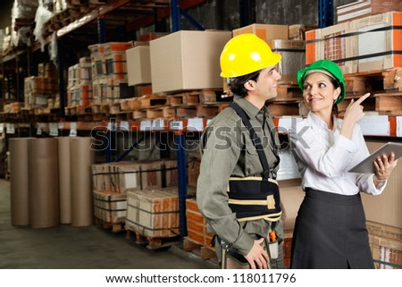 Female supervisor with foreman pointing at stock on shelves in warehouse - stock photo