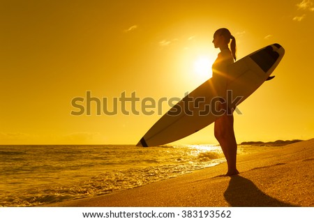 Female surfer looking out at the beautiful ocean. - stock photo