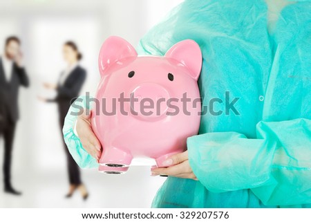 Female surgeon doctor with piggy bank. - stock photo
