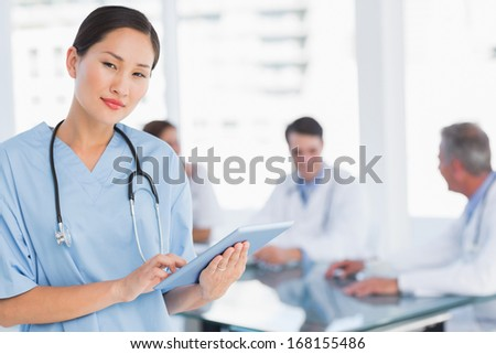 Female surgeon using digital tablet with group around table in background at hospital - stock photo