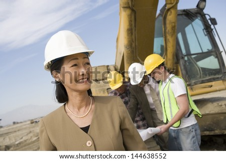 Female surveyor and construction workers on site - stock photo