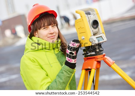 female surveyor worker working with theodolite transit equipment at road construction site outdoors - stock photo