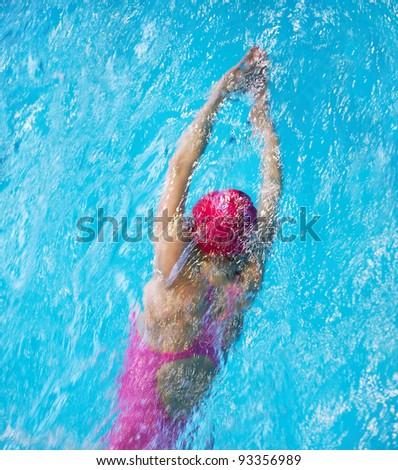 Female swimmer in pink swimwear in pool - stock photo