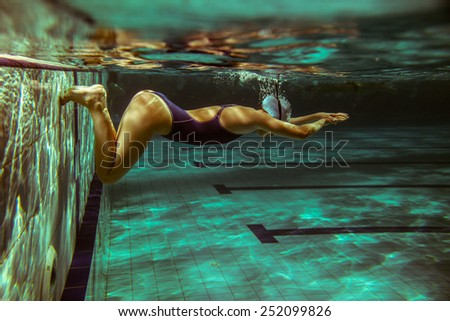 Female swimmer in swimming pool.Underwater image.Grain effect added for artistic impression. - stock photo