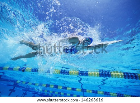 Female swimmer in United States swimsuit while swimming in pool - stock photo