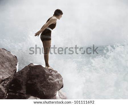 Female swimmer on rock above crashing surf - stock photo