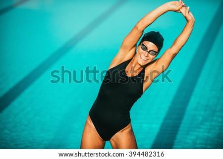 Female swimmer streching on poolside  - stock photo