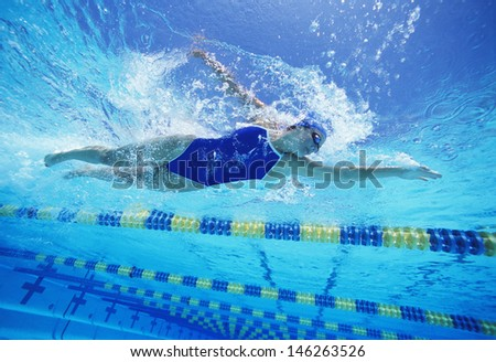 Female swimmer wearing United States swimsuit while swimming in pool - stock photo