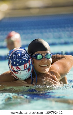 Female swimmers embracing each other in pool - stock photo