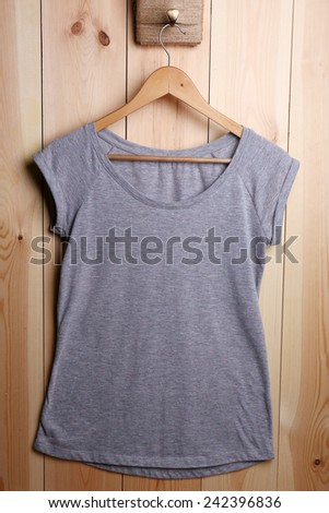 Female t-shirt on hanger on wooden wall background - stock photo