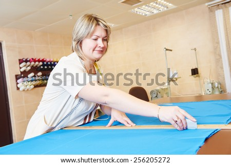 female tailor working with cloth fabric in workshop