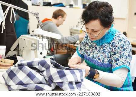 female tailor working with cloth in sewing workshop - stock photo