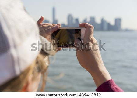 Female taking pictures of city with smart phone - stock photo