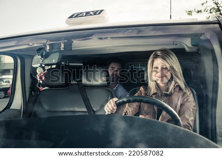 Female taxi driver with passenger - stock photo