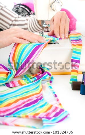 Female taylor working on a sewing machine - stock photo