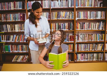 Female teacher and little girl reading book in the library