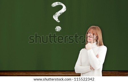 female teacher in front of a blackboard with a question mark - stock photo