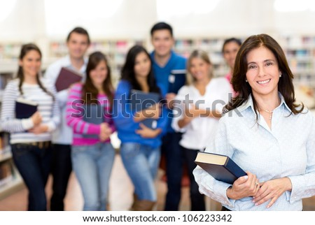 Female teacher smiling with a group of university students - stock photo