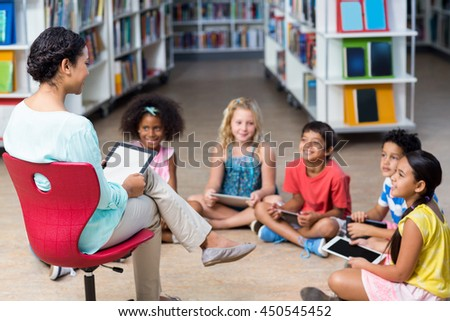 Female teacher with children using digital tablets in library