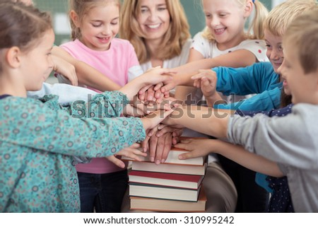 Female Teacher with her Pupils Putting their Hands on Top of One Another on a Stack of Books Inside the Classroom. - stock photo