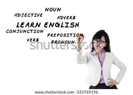 Female teacher writes english language materials on whiteboard - stock photo