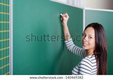 female teacher writing on blackboard in classroom - stock photo