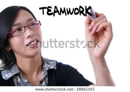 female teacher writing the word Teamwork - stock photo