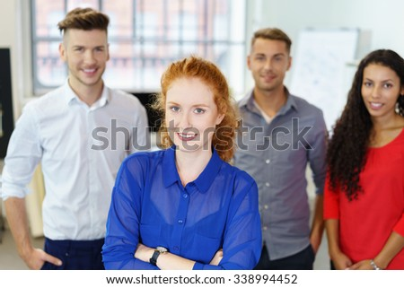 female teamleader standing with crossed arms with coworkers in background - stock photo