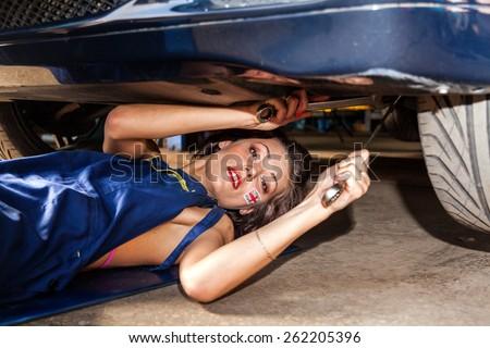Female technician checks the suspension of the car in service. - stock photo