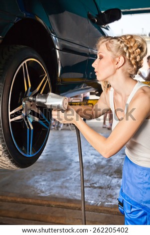 Female technician replaces the wheel of the vehicle in service. - stock photo