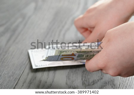 female teen hand hold dollar banknotes, over wooden table