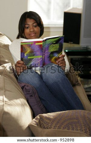 female teen youth reading book while relaxing on couch - stock photo