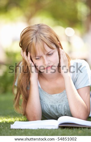 Female Teenage Student Studying In Park Looking Puzzled - stock photo