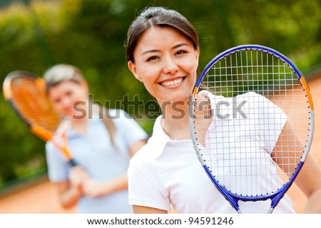 Female tennis player at the court playing doubles - stock photo