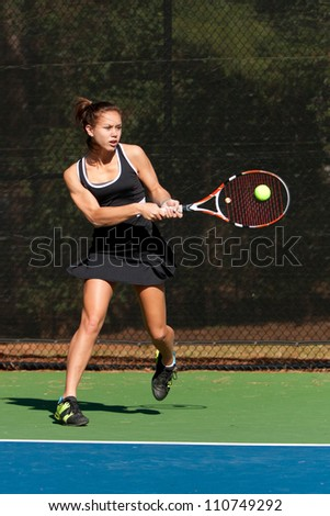 Female Tennis Player Hits Powerful Backhand During Match - stock photo